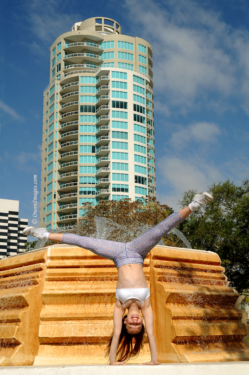 Gymnast doing a cartwheel on the edge of a fountain in downtown St Petersburg, Florida