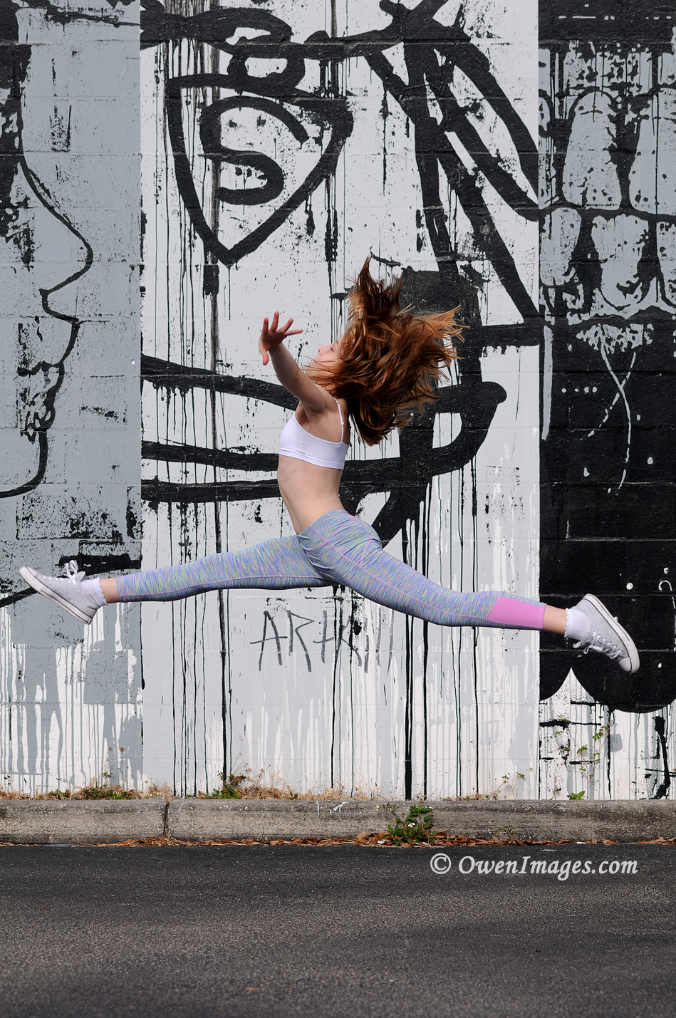 Gymnast leaping in front of a mural in downtown Saint Petersburg, Florida