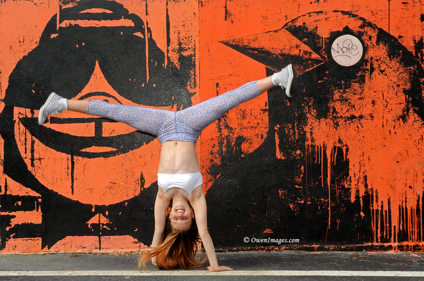 Gymnast doing a cartwheel in front of a mural in downtown Saint Petersburg, Florida