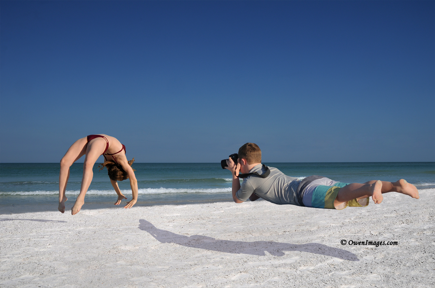 Impossible Becomes Possible - Boy diving to photograph girl performing a back handspring on the beach. @OwenImages