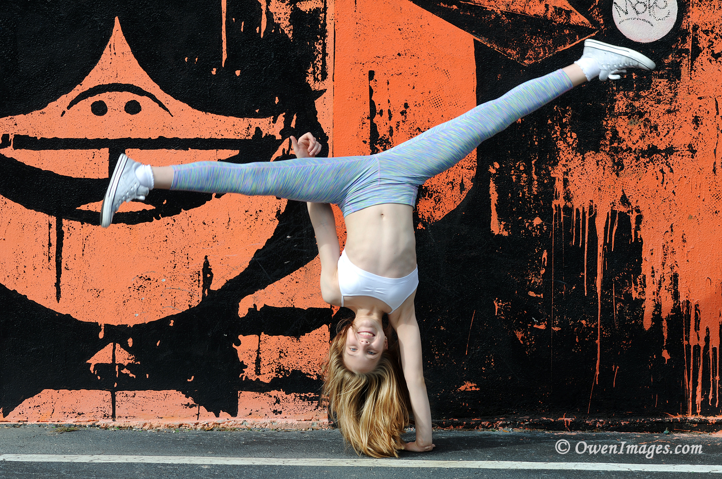Gymnast doing a one arm cartwheel in front of a mural in downtown Saint Petersburg, Florida