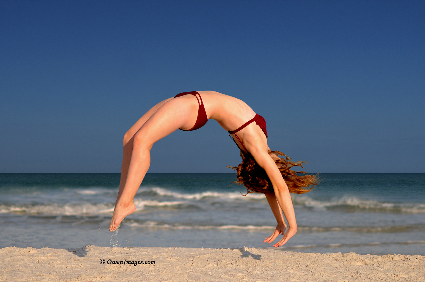 Athlete performing a back handspring on the beach shortly after sunrise. @OwenImages