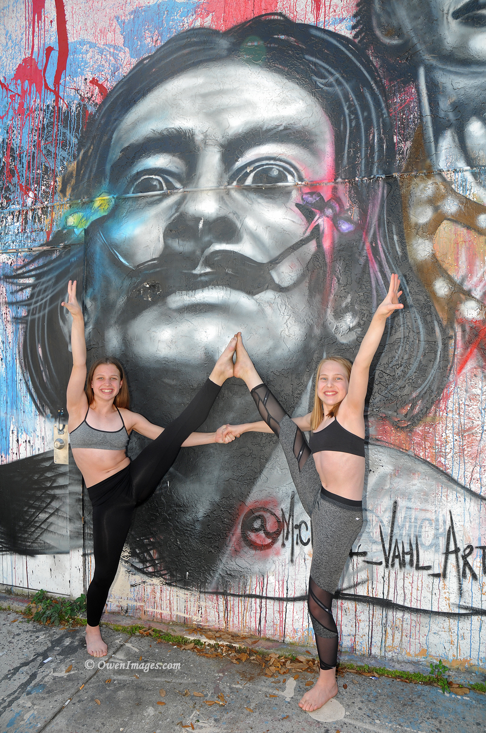 Two gymnasts pose in front of an alley mural depicting Dalí in downtown Saint Petersburg, Florida